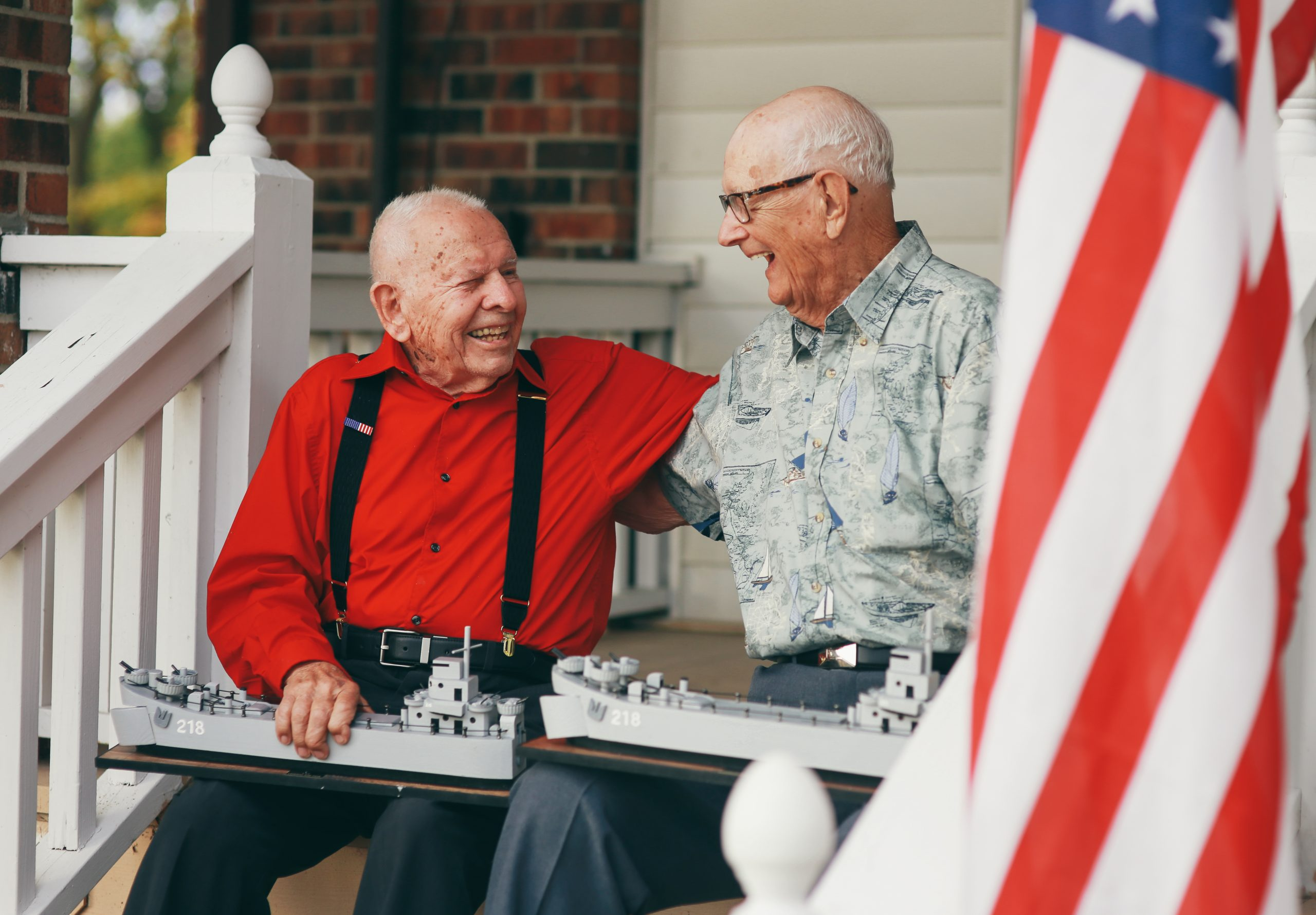 John and DeVere from the movie, The Last Signal, are sitting together embracing on the front porch, holding scaled models of the Navy ship they were on together.