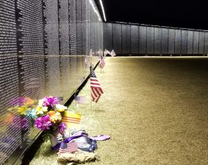 The Wall That Heals at night with flags and flowers left at the base of the Vietnam Veterans Memorial Replica