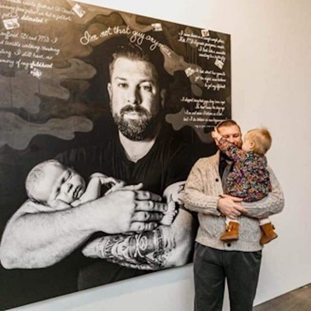 Josh Sandor and daughter Emma in front of their portrait in Depicting the Invisible